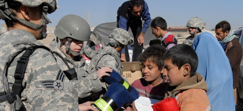 KABUL PROVINCE, Afghanistan (Dec.18, 2010) -- Two young Afghan refugees receive blankets from American soldiers. Military memebers of International Security Assistance Force ventured today into the refugee camp to bring food, school supplies, clothing and blankets.The installation chaplain at the ISAF Headquarters aims to make these supply visits monthly to help out those in need.  (US Air Force Photo by Staff Sgt. Stacey Haga)